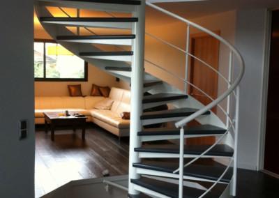 Escalera caracol con peldaños de madera Modelo MGD Bois, con barandilla H2 y Pasamano Metálico.